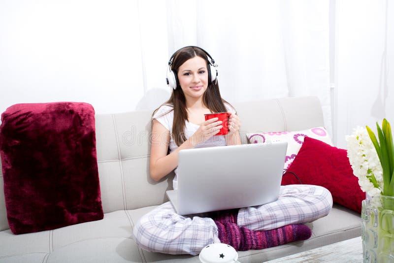 Musica d'ascolto a casa con il computer portatile immagine stock