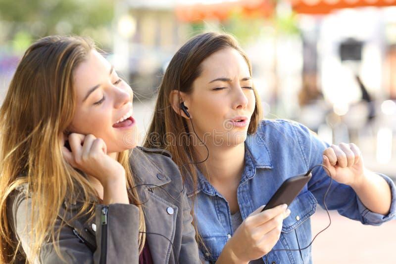 Musica d'ascolto degli amici sulla linea e sul canto fotografie stock