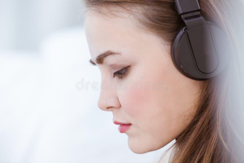 Musica d'ascolto del bello ritratto della donna del primo piano con il primo piano della cuffia fotografia stock libera da diritti