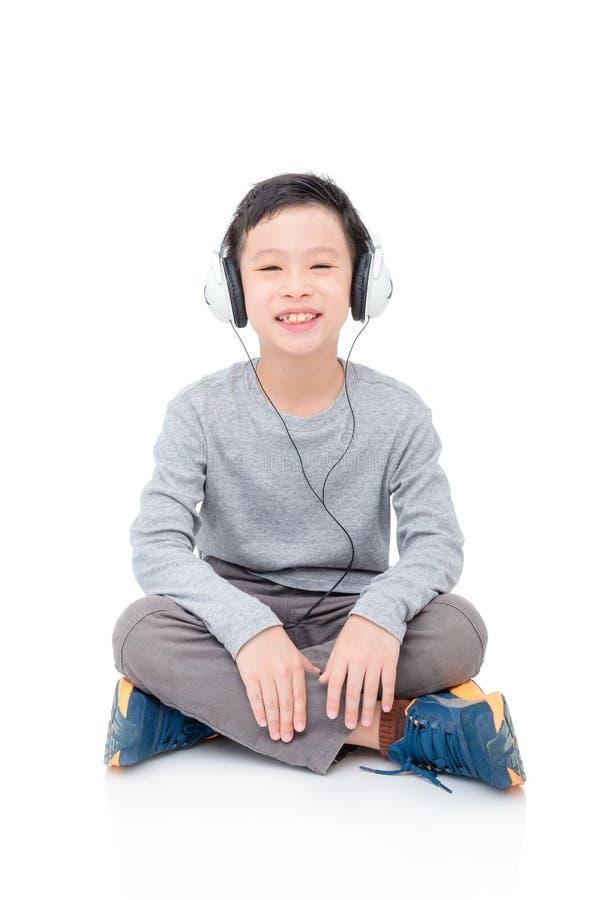 Musica d'ascolto del giovane ragazzo dalle cuffie fotografia stock