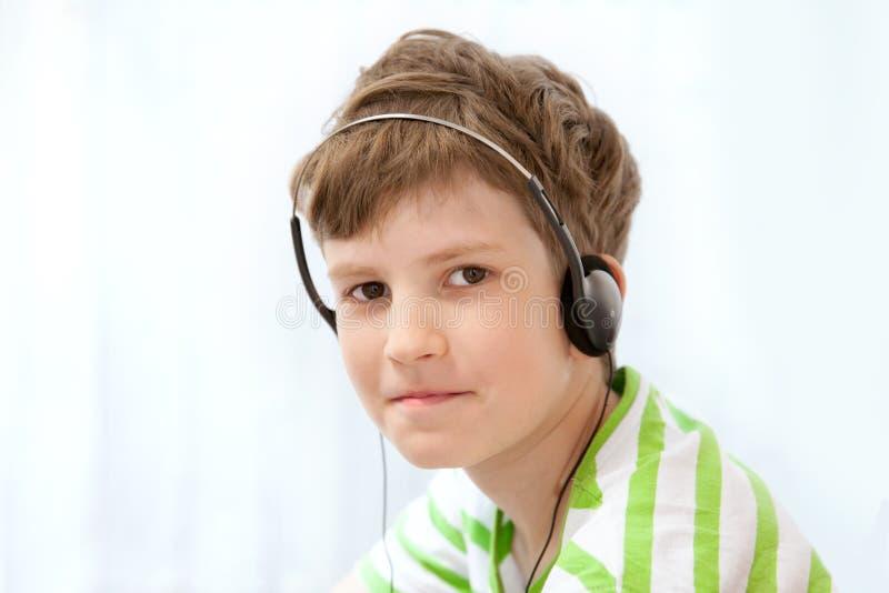 Musica d'ascolto del giovane ragazzo sulle cuffie fotografia stock