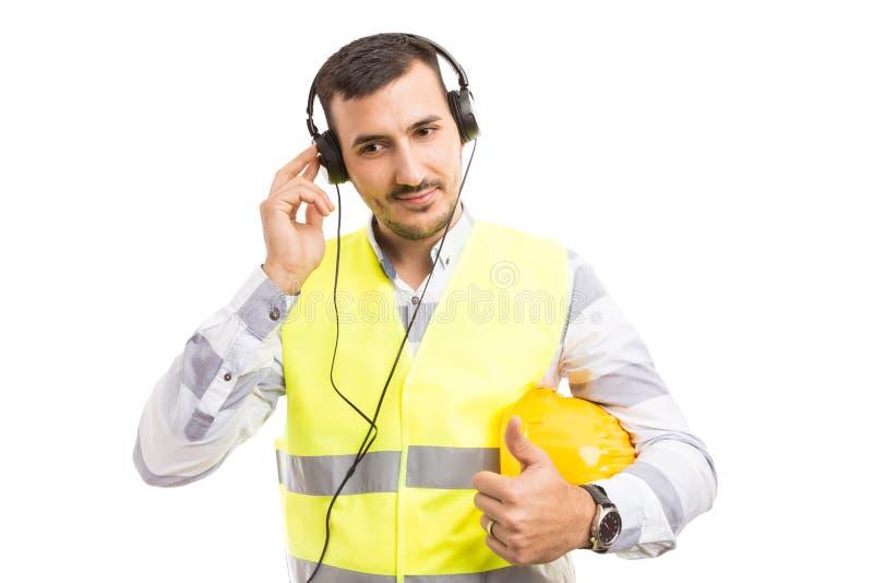 Musica d'ascolto del muratore bello sulle cuffie immagine stock libera da diritti