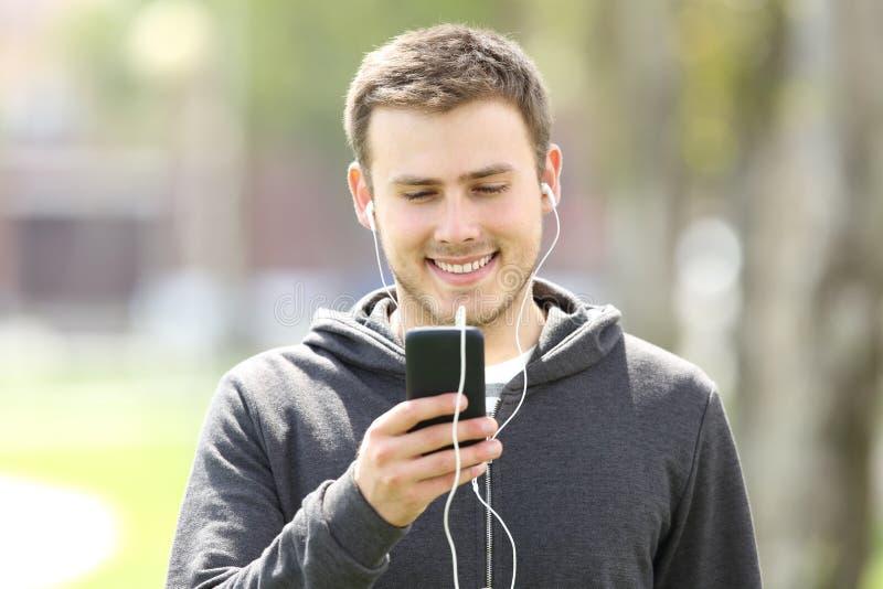 Musica d'ascolto del ragazzo teenager sulla linea con i earbuds immagine stock