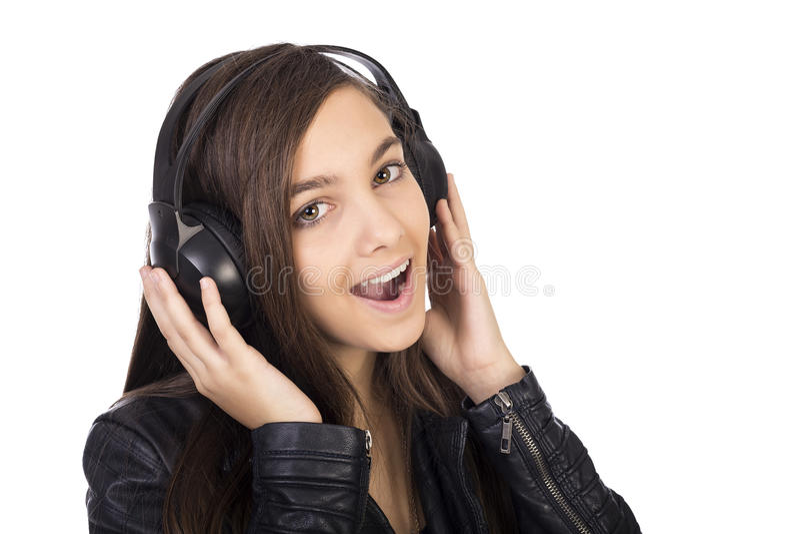 Musica d'ascolto dell'adolescente grazioso sulle suoi cuffie e singi fotografia stock