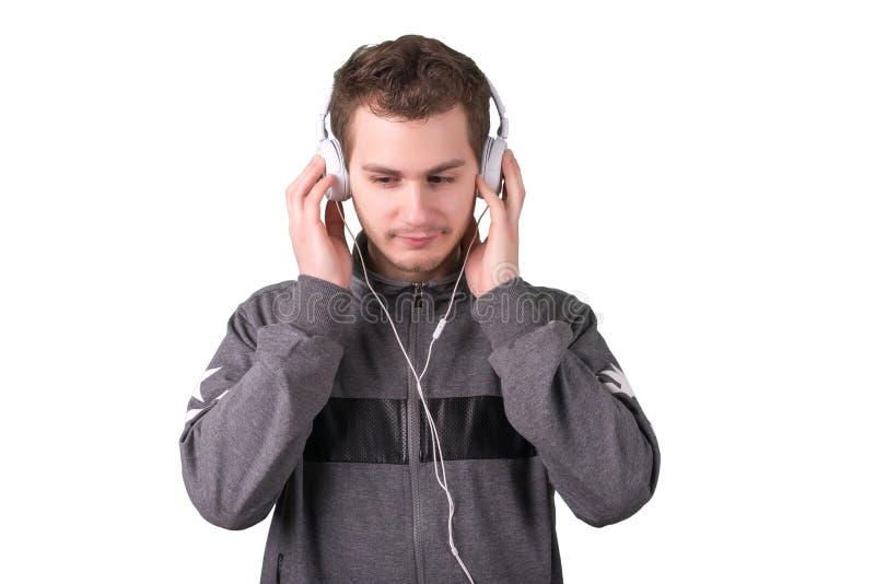 Musica d'ascolto dell'uomo bello su fondo bianco fotografie stock