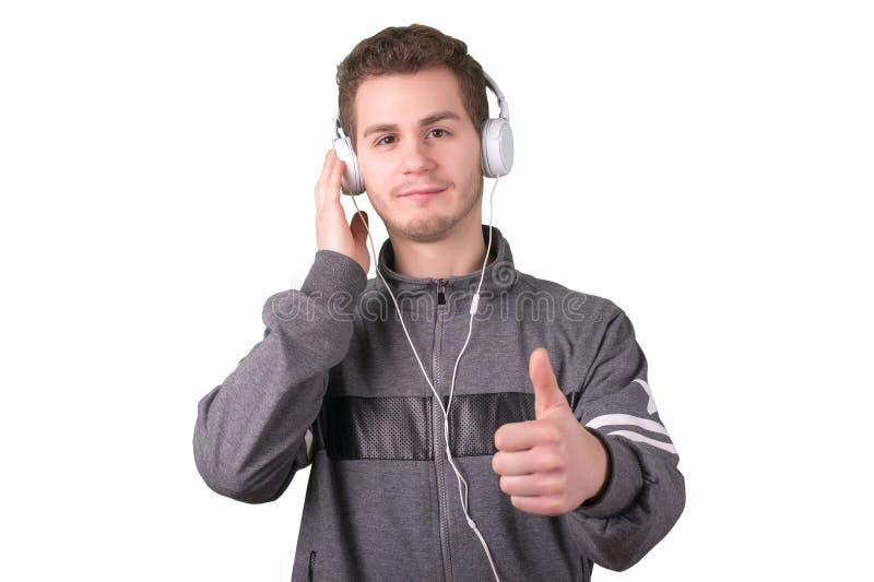 Musica d'ascolto dell'uomo bello su fondo bianco immagine stock