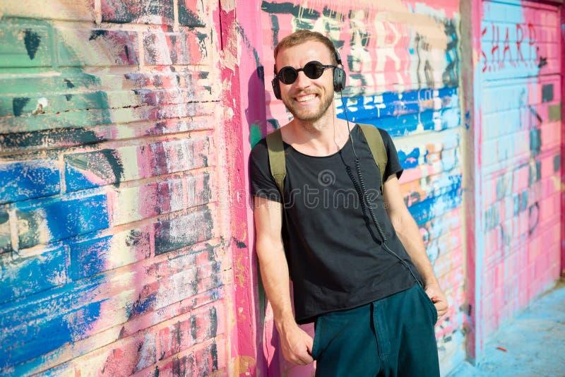 Musica d'ascolto dell'uomo biondo alla moda moderno dei pantaloni a vita bassa fotografie stock