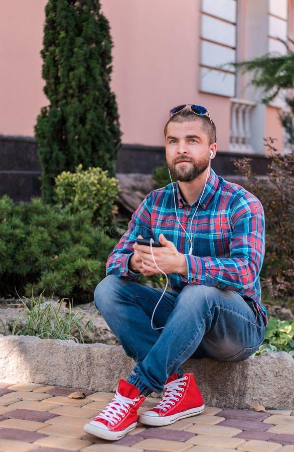Musica d'ascolto dell'uomo dei pantaloni a vita bassa con le sue cuffie fotografia stock libera da diritti