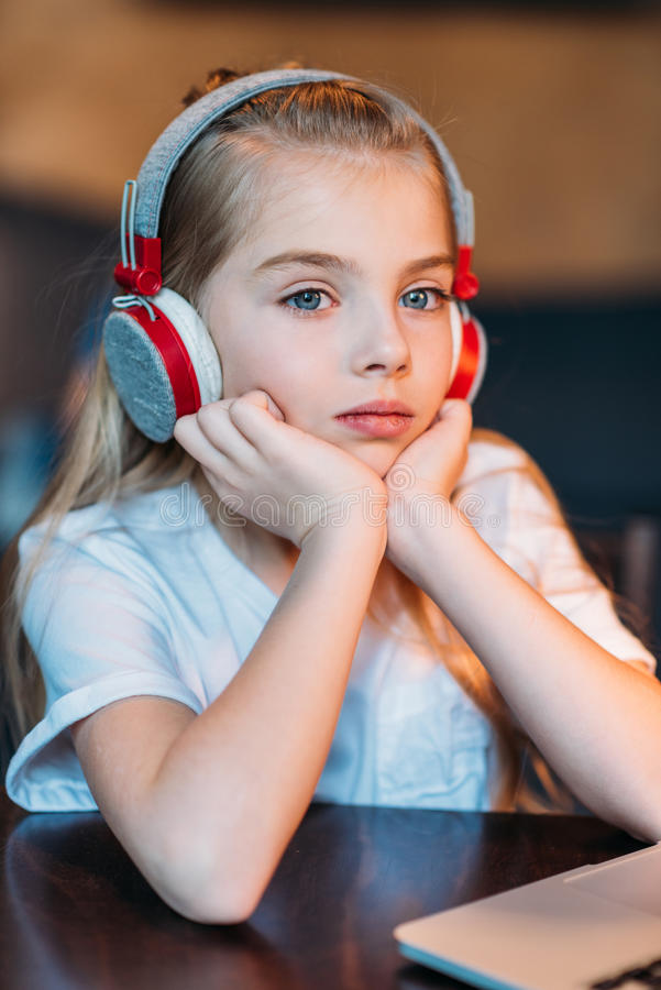 Musica d'ascolto della bambina pensierosa in cuffie fotografia stock