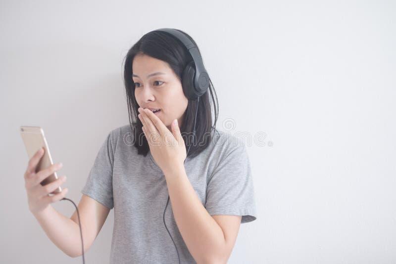 Musica d'ascolto della bella donna asiatica con la cuffia e lo smartphone su un fondo bianco con lo spazio della copia fotografia stock
