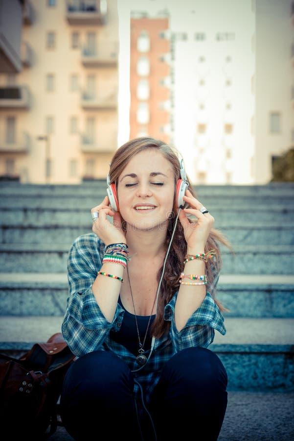 Musica d'ascolto della bella giovane donna bionda dei pantaloni a vita bassa immagini stock