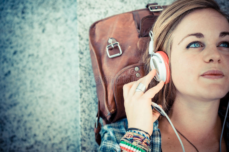 Musica d'ascolto della bella giovane donna bionda dei pantaloni a vita bassa fotografie stock libere da diritti