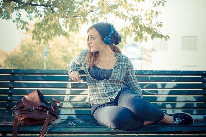 Musica d'ascolto della bella giovane donna bionda dei pantaloni a vita bassa immagine stock libera da diritti