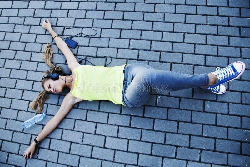 Musica d'ascolto della bella giovane donna felice nella cuffia Uff fotografia stock libera da diritti