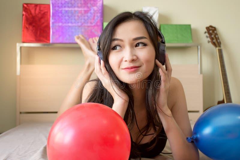 Musica d'ascolto della donna abbastanza asiatica in cuffie sul letto con il pallone fotografie stock libere da diritti