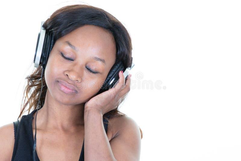 Musica d'ascolto della donna africana chiusa degli occhi sulla cuffia immagini stock