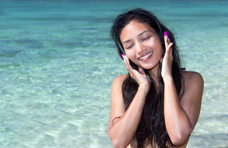 Musica d'ascolto della donna felice fotografia stock libera da diritti