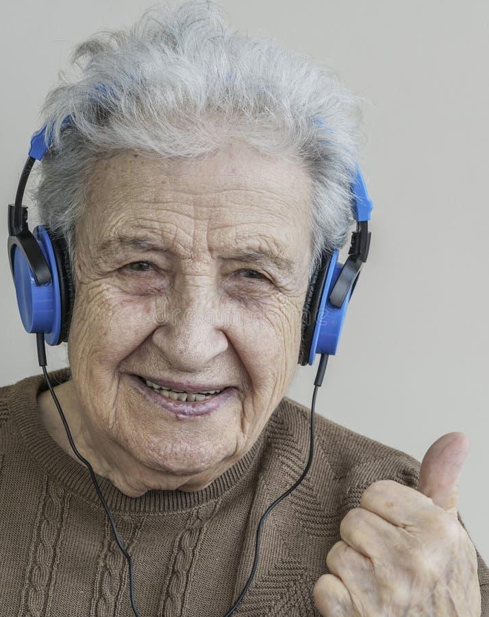 Musica d'ascolto della donna senior felice con le cuffie fotografia stock