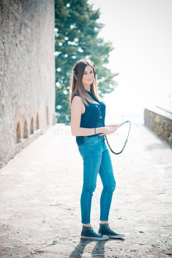 Musica d'ascolto della giovane bella donna dei pantaloni a vita bassa immagine stock