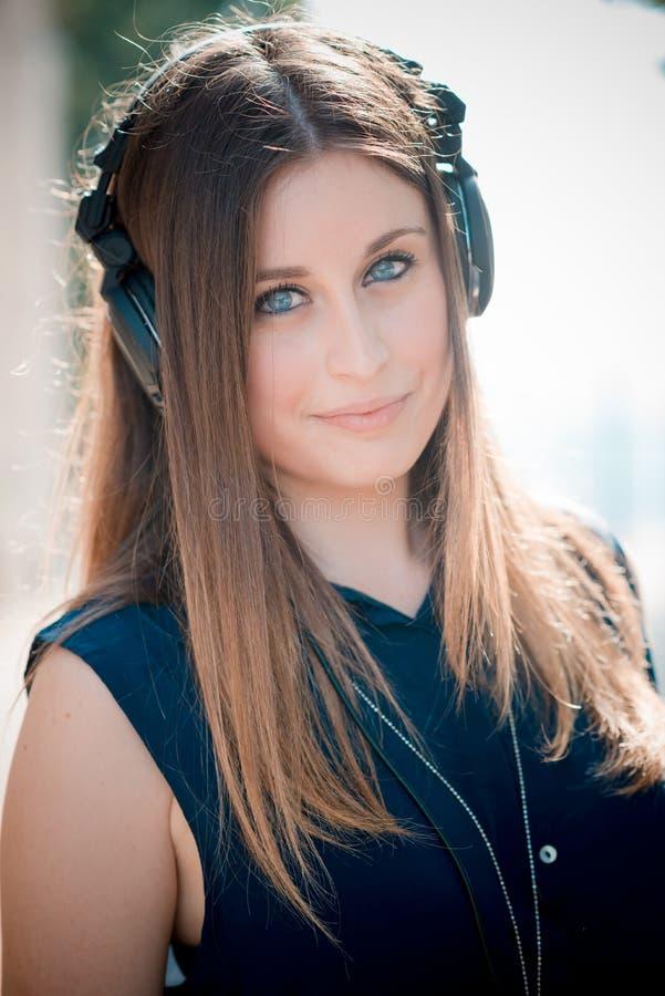 Musica d'ascolto della giovane bella donna dei pantaloni a vita bassa immagini stock libere da diritti
