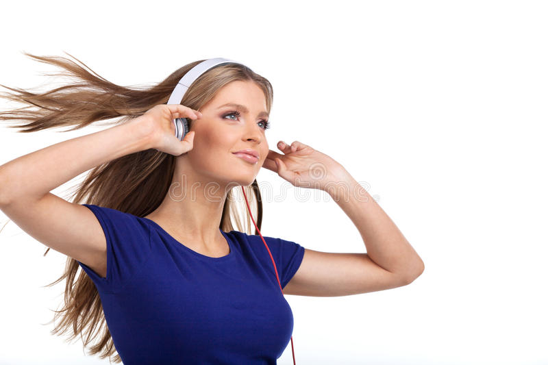 Musica d'ascolto della giovane donna allegra con le cuffie immagini stock libere da diritti
