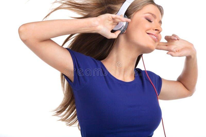 Musica d'ascolto della giovane donna allegra con le cuffie fotografia stock libera da diritti