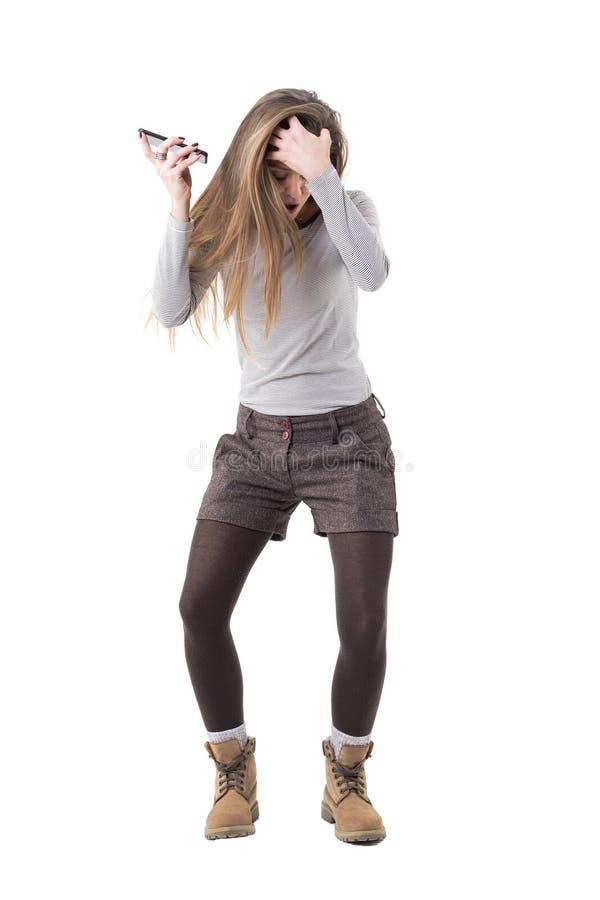Musica d'ascolto della giovane donna dei pantaloni a vita bassa sull'altoparlante del telefono cellulare nella gioia fotografie stock libere da diritti