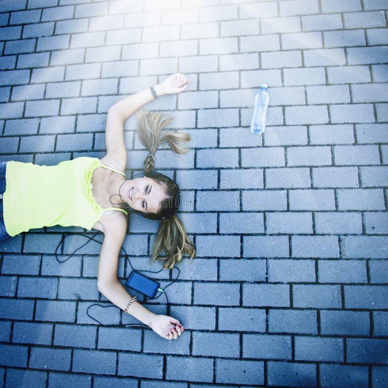 Musica d'ascolto della giovane ragazza attraente felice con la cuffia fotografie stock libere da diritti