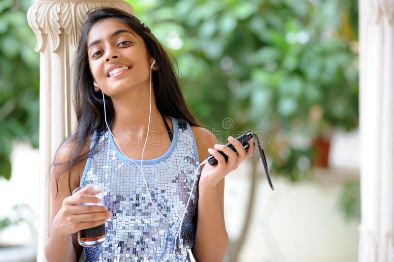 Musica d'ascolto della ragazza all'esterno immagine stock libera da diritti