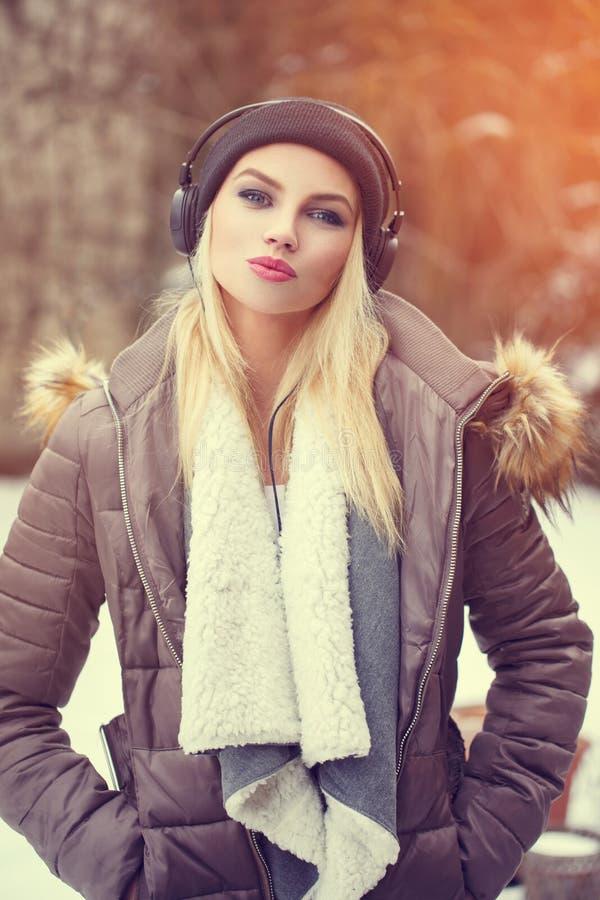 Musica d'ascolto della ragazza d'avanguardia dei pantaloni a vita bassa all'inverno fotografia stock libera da diritti