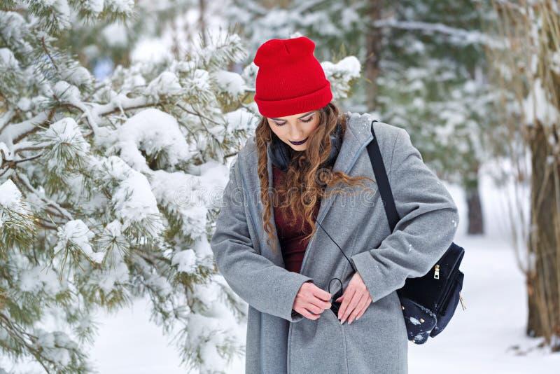 Musica d'ascolto della ragazza dei pantaloni a vita bassa nell'inverno fotografia stock