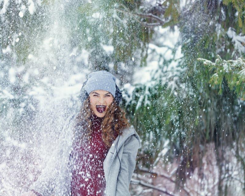 Musica d'ascolto della ragazza dei pantaloni a vita bassa nell'inverno immagine stock libera da diritti