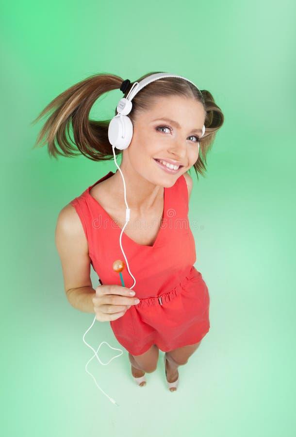 Musica d'ascolto della ragazza divertente su fondo verde fotografia stock