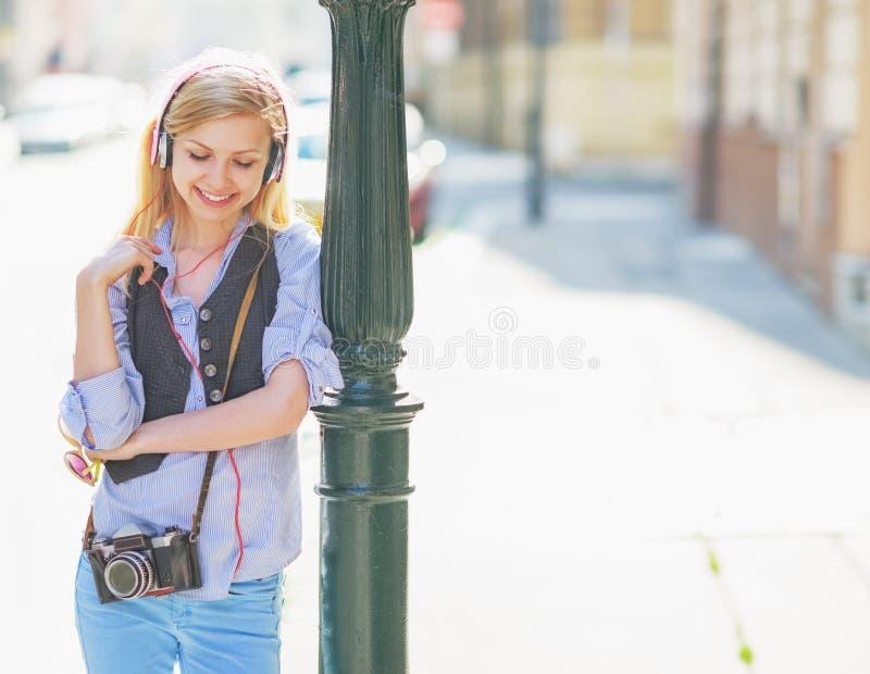 Musica d'ascolto della ragazza felice dei pantaloni a vita bassa sulla via della città immagine stock libera da diritti