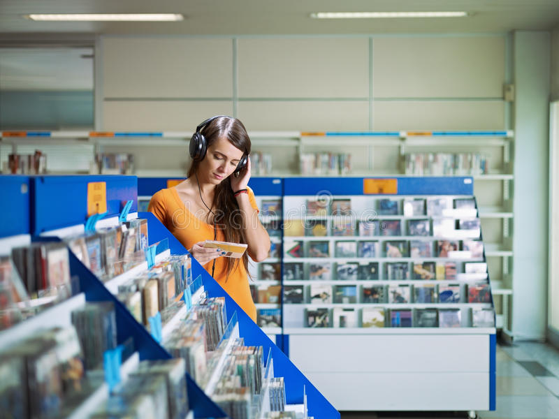 Musica d'ascolto della ragazza in memoria cd fotografie stock