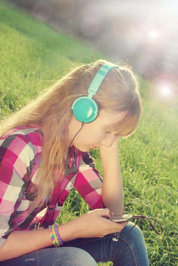 Musica d'ascolto della ragazza sul prato nello stile d'annata fotografia stock libera da diritti