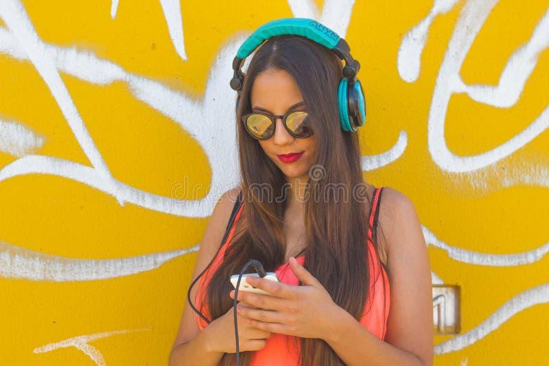 Musica d'ascolto della ragazza in suo telefono cellulare fotografie stock libere da diritti