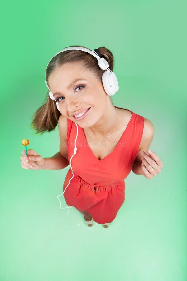 Musica d'ascolto della ragazza variopinta divertente su fondo verde fotografie stock