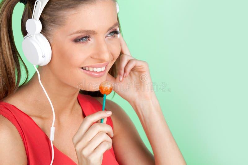 Musica d'ascolto della ragazza variopinta divertente su fondo verde Donna sexy che ascolta la musica sulle cuffie e che lecca lec immagini stock libere da diritti
