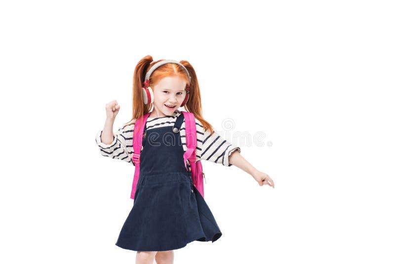 musica d'ascolto della scolara felice adorabile in cuffie e nel ballare fotografia stock libera da diritti