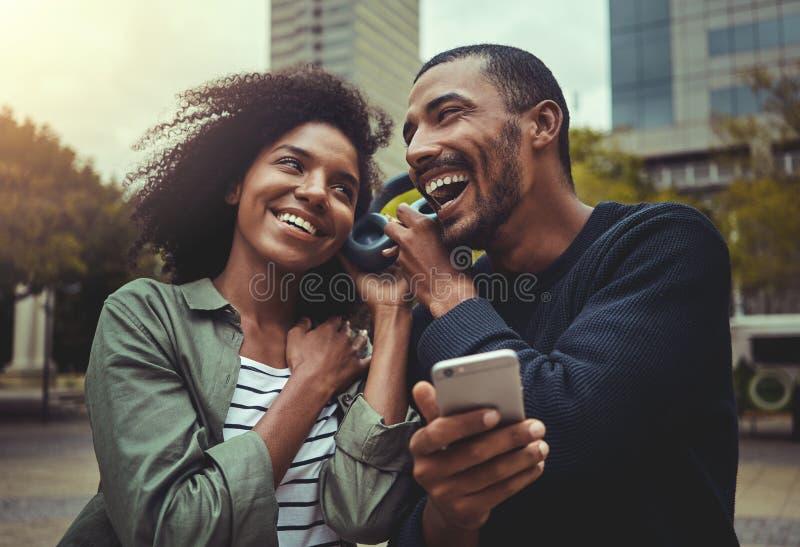 Musica d'ascolto delle giovani coppie su una cuffia immagini stock