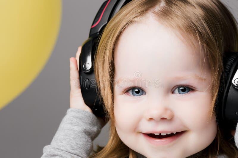 Musica d'ascolto sorridente felice della ragazza in grandi cuffie immagine stock libera da diritti