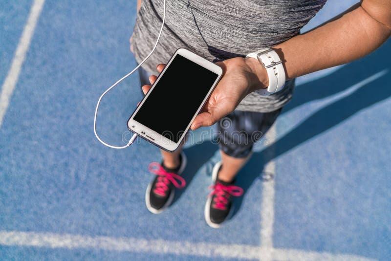 Musica dello schermo del telefono della ragazza del corridore per eseguire pista fotografie stock