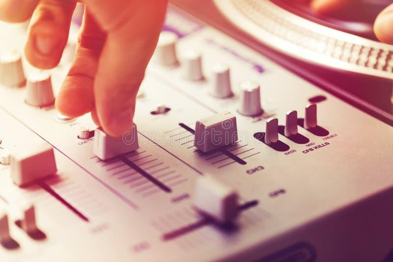 Musica di gioco e mescolantesi del DJ sul regolatore della piattaforma girevole immagini stock libere da diritti