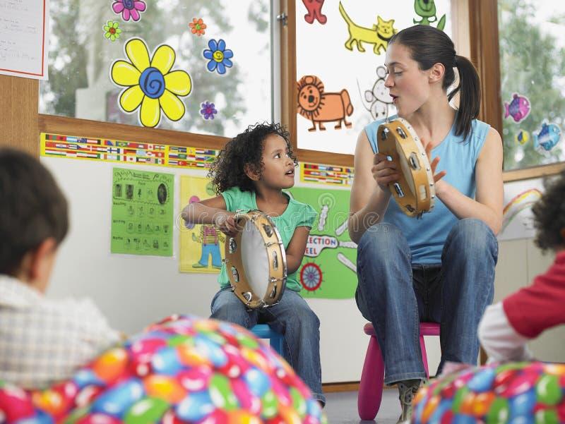 Musica di With Girl Playing dell'insegnante nella classe fotografie stock libere da diritti