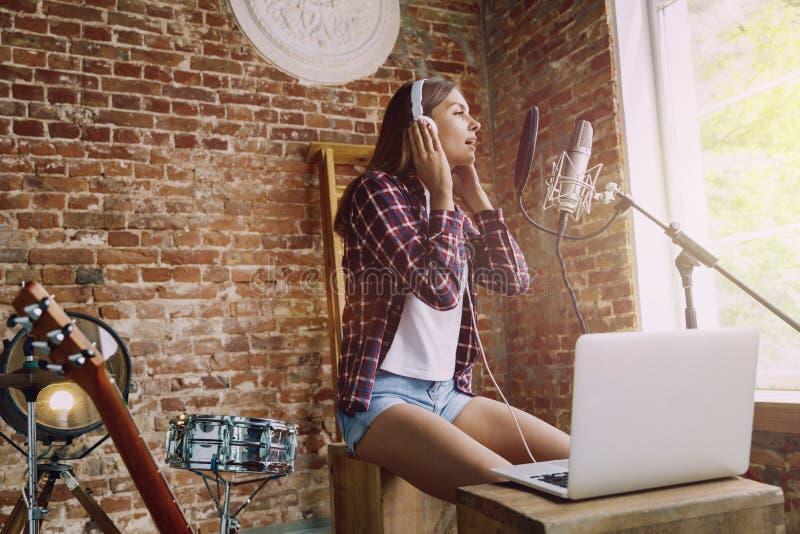 Musica di registrazione della donna, trasmettendo per radio e cantando a casa fotografie stock libere da diritti