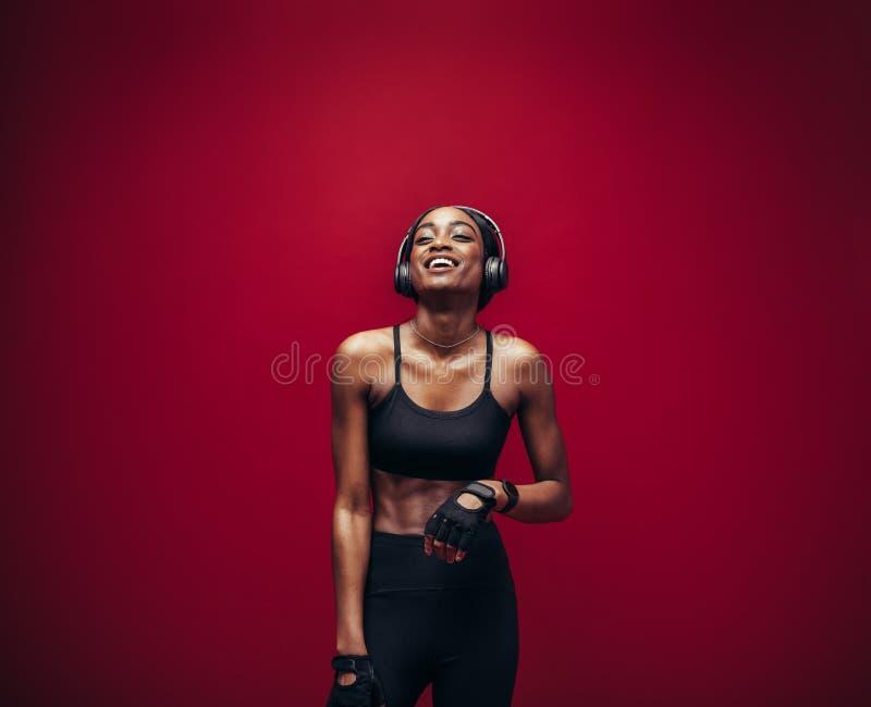 Musica di rilassamento e d'ascolto della donna di forma fisica dopo il suo allenamento fotografie stock