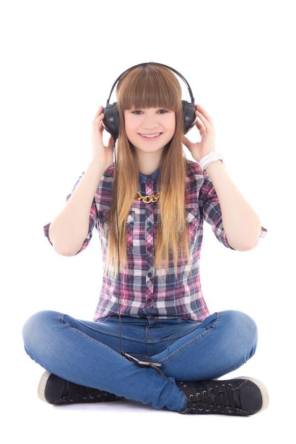 Musica di seduta e d'ascolto dell'adolescente sveglio con le cuffie fotografie stock libere da diritti