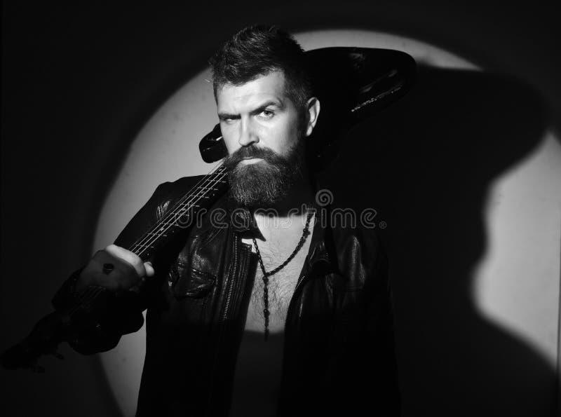 Musica e concetto di stile del hard rock Il musicista e lo strumento musicale alla luce hanno diretto su lui fotografie stock