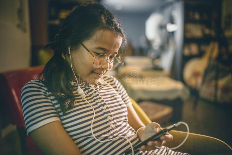Musica lissening dell'adolescente asiatico dal telefono a mani libere dell'orecchio in Li domestico immagine stock libera da diritti